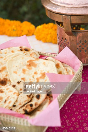 Roti and naan in basket on decorated table