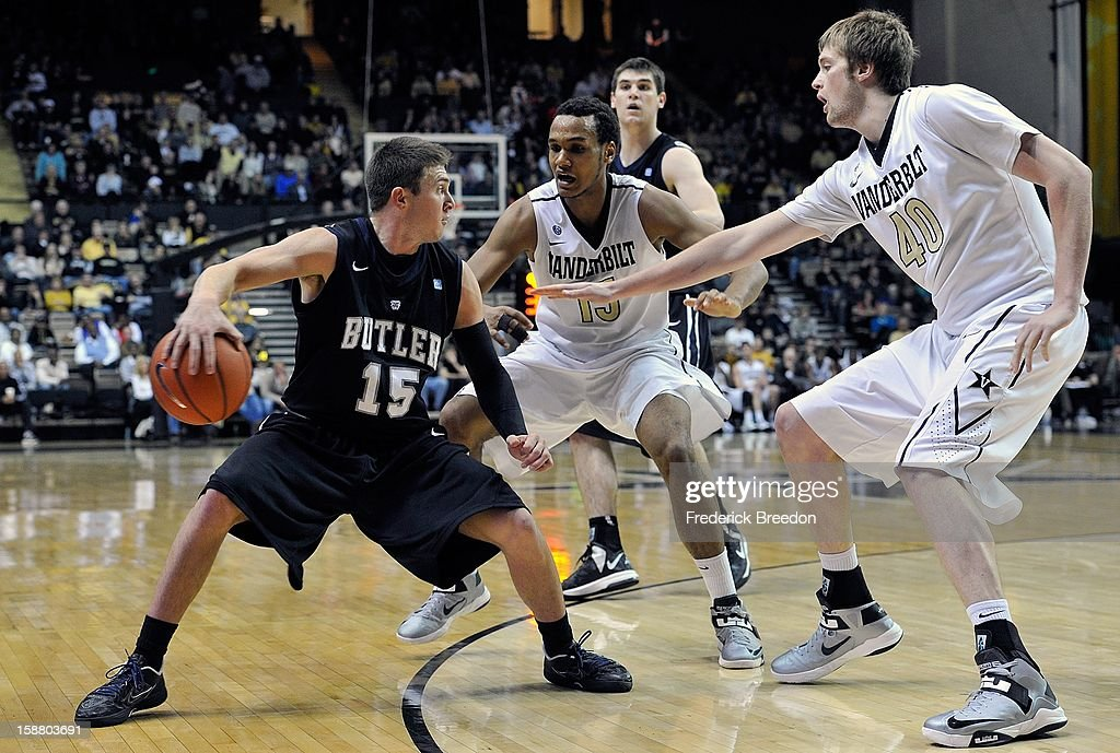 Rotnei Clarke #15 of the Butler Bulldogs makes a no look pass behind his back past Kevin Bright #15 and Josh Henderson #40 of the Vanderbilt Commodores at Memorial Gym on December 29, 2012 in Nashville, Tennessee.