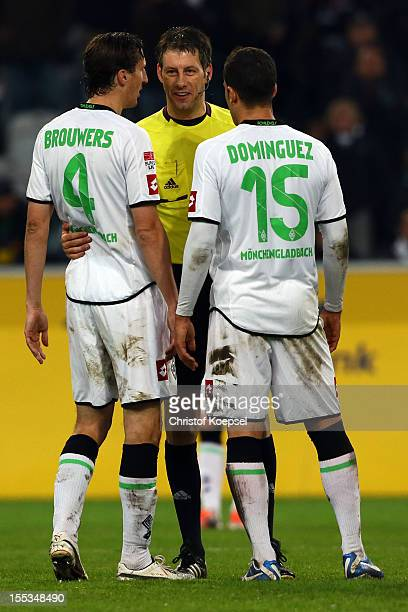 Rouel Brouwers and Alvaro Dominguez of Moenchengladbach discuss with referee Wolfgang Stark after the Bundesliga match between VfL Borussia...