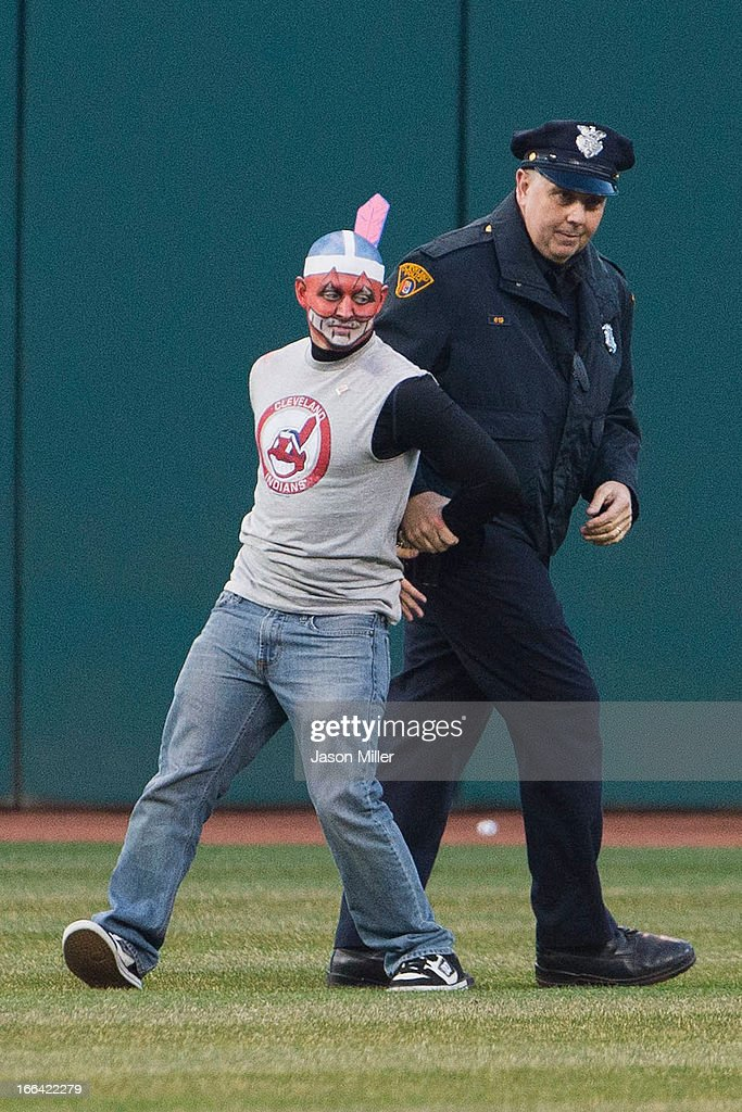 A rouge fan is arrested by a Cleveland police officer after entering the playing filed during the eighth inning of the game between the Cleveland Indians and the New York Yankees on opening day at Progressive Field on April 8, 2013 in Cleveland, Ohio.