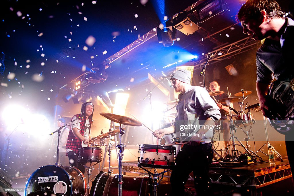 Roughton 'Rou' Reynolds, guitar teck and Rob Rolfe of Enter Shikari Perform onstage during a day of the 5th UK leg of their A Flash Flood of Colour World Tour called A Flash Flood Of Christmas; at Rock City on December 12, 2012 in Nottingham, England.