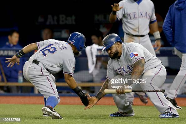 Rougned Odor celebrates with Prince Fielder of the Texas Rangers after Odor comes in to score after the throw by Russell Martin of the Toronto Blue...