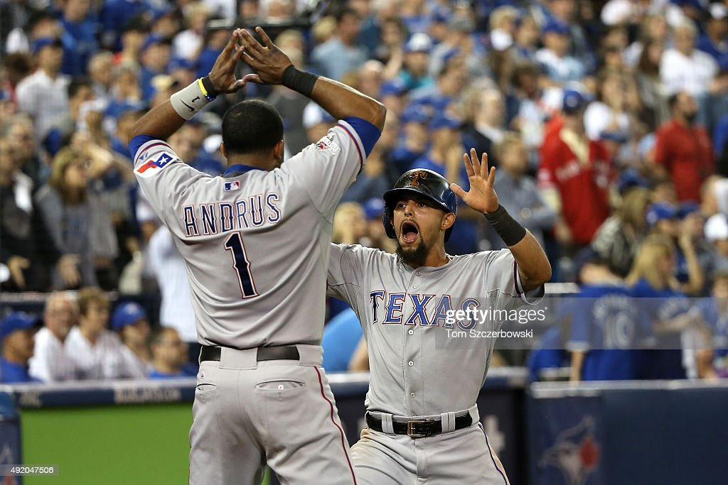 Rougned Odor of the Texas Rangers celebrates scoring the go ahead run in the 14th inning with Elvis Andrus against the Toronto Blue Jays during game...