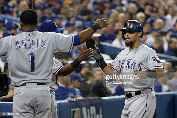 Rougned Odor of the Texas Rangers celebrates with his teammates after scoring a run off of an RBI single hit by Delino DeShields in the third inning...