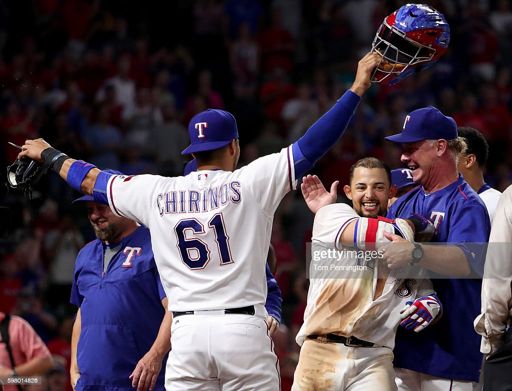 Rougned Odor of the Texas Rangers celebrates with Robinson Chirinos of the Texas Rangers and Steve Buechele of the Texas Rangers after hitting a...
