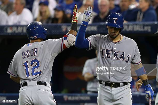 Rougned Odor of the Texas Rangers celebrates with teammate Robinson Chirinos after scoring a solo home run against David Price of the Toronto Blue...