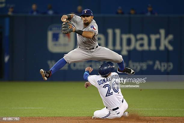 Rougned Odor of the Texas Rangers collides with Josh Donaldson of the Toronto Blue Jays after taggin him out in the fourth inning during game one of...