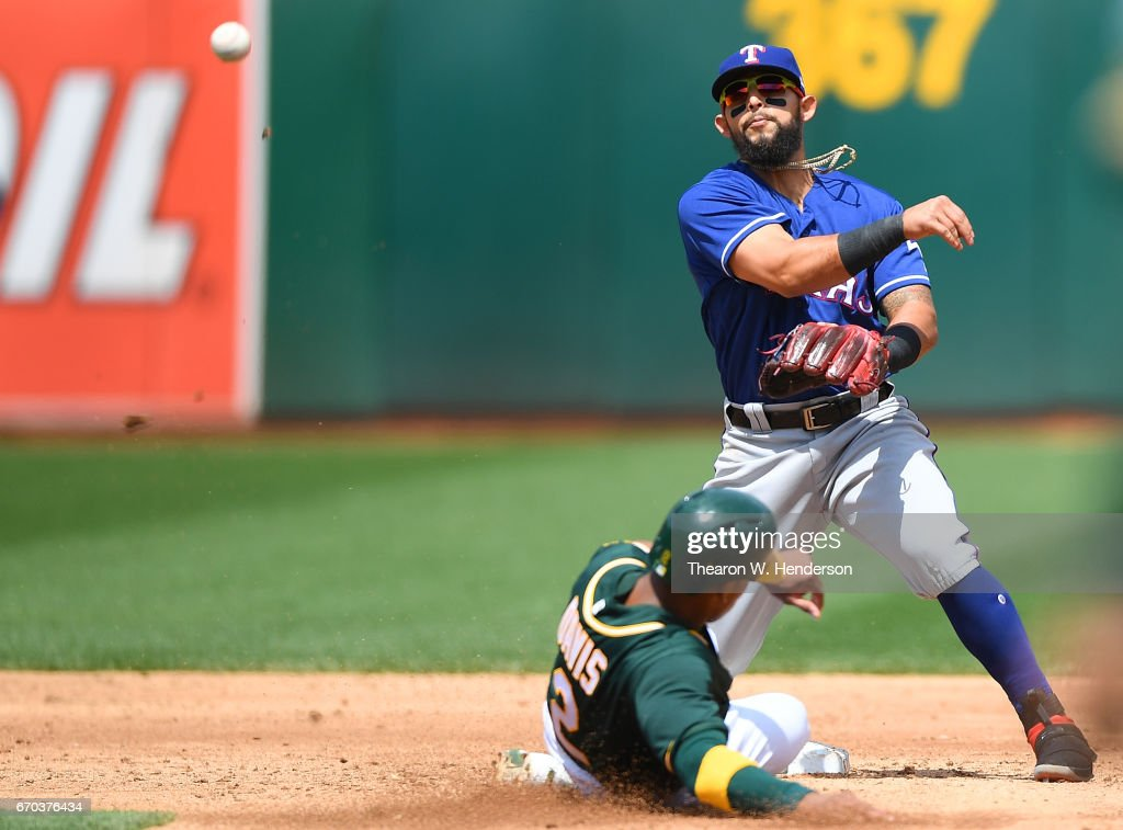 Rougned Odor #12 of the Texas Rangers completes the double-play by getting his throw off over the top of Khris Davis #2 of the Oakland Athletics in the bottom of the third inning at Oakland Alameda Coliseum on April 19, 2017 in Oakland, California.