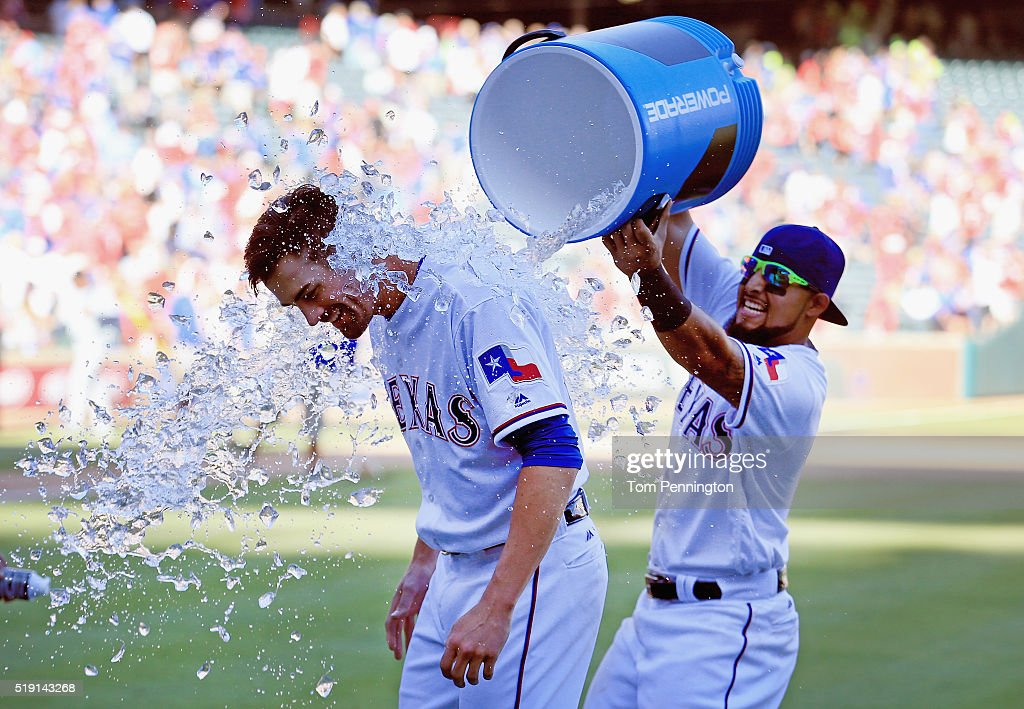 Rougned Odor of the Texas Rangers dunks starting pitcher Cole Hamels of the Texas Rangers with a water cooler after the Rangers beat the Seattle...