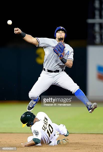 Rougned Odor of the Texas Rangers gets his throw off over the top of Marcus Semien of the Oakland Athletics but not in time to complete the...