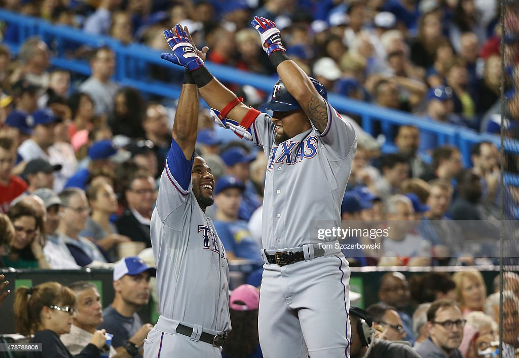 Rougned Odor of the Texas Rangers is congratulated by Elvis Andrus after hitting a solo home run in the seventh inning during MLB game action against...