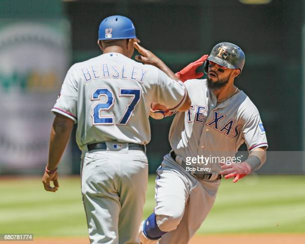 Rougned Odor of the Texas Rangers salutes third base coach Tony Beasley after hitting a first inning home run against the Houston Astros at Minute...