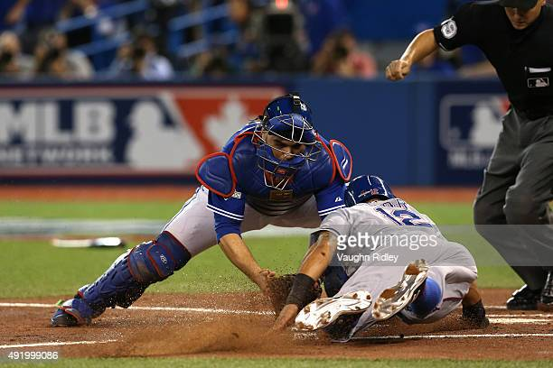 Rougned Odor of the Texas Rangers slides around Russell Martin of the Toronto Blue Jays to score in the second inning during game two of the American...