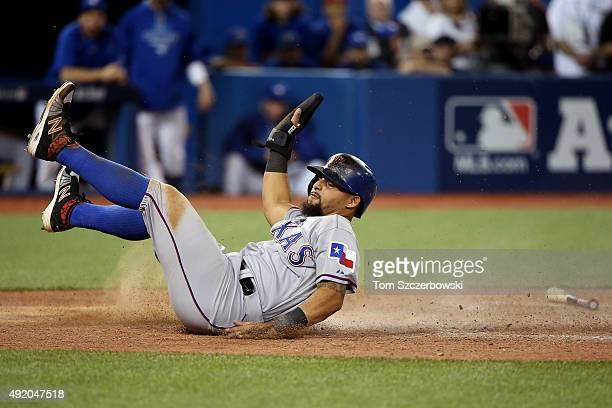 Rougned Odor of the Texas Rangers slides home safely with the go ahead run in the top of the 14th inning against the Toronto Blue Jays during game...