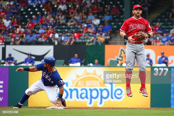 Rougned Odor of the Texas Rangers slides in safe and advancing to third base on a over throw to Johnny Giavotella of the Los Angeles Angels of...