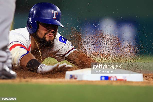 Rougned Odor of the Texas Rangers slides into third base after hitting a triple against the Chicago White Sox in the bottom of the eighth inning at...