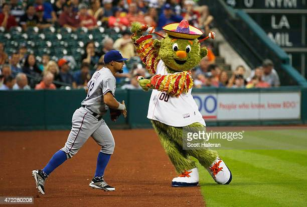 Rougned Odor of the Texas Rangers trots out to the field past the dancing Houston Astros mascot Orbit during the first inning of their game at Minute...