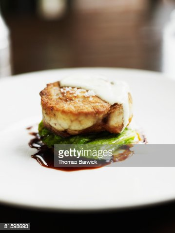 Roulade of veal sweetbreads and chicken mousse with fried green tomato, apricot puree, romaine and egg sauce : Stock Photo