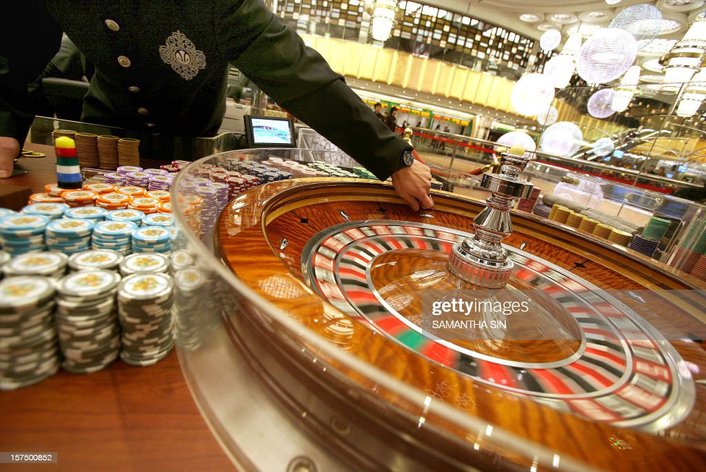 A roulette dealer waits at one of the new tables at the Grand Lisboa hotel and casino during a press preview ahead of the casino's opening in Macau...
