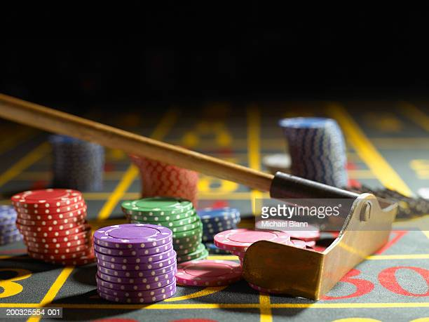 Roulette rake gathering gambling chips on table, close-up