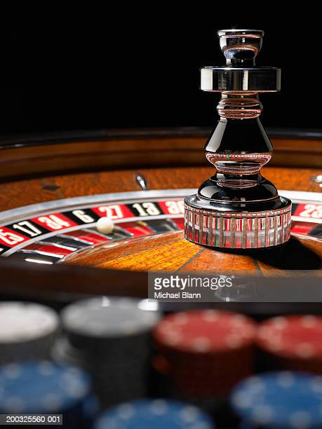 Roulette wheel, gambling chips in foreground (focus on wheel)