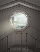 Round attic window, light shining in
