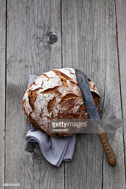 Round crusty bread, old bread knife and kitchen towel on wood