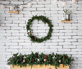 Closeup view of round elegant Christmas wreath hanging on white brick wall. Wreath decorated with ratten balls, dried flowers of lotus and wooden star. Beautiful long garland on top of fireplace.