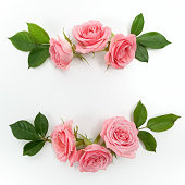 Round frame made of pink roses, green leaves, branches, floral pattern on white background. Flat lay
