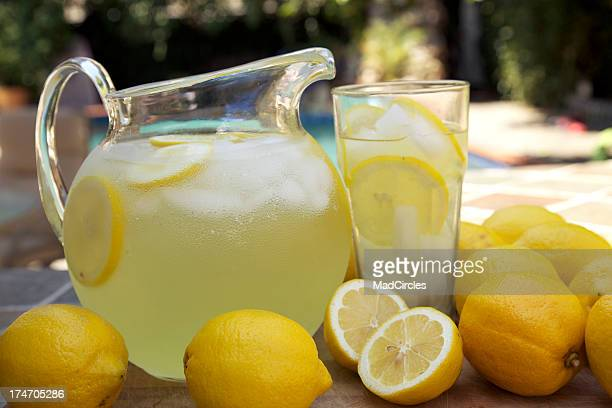 Round glass jug of fresh lemonade with sliced lemons at pool