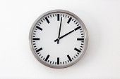 Round metal clock on white wall