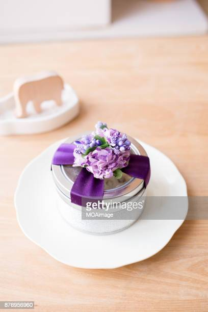 A round metal gift box on a white plate is placed on the wooden table