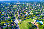 Round Rock , Texas , USA aerial drone view high above Suburb Neighborhood with Vast amount of Homes - Summertime in the best place to live in America - at all way stop or crossroads
