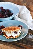 Homemade Round waffles with fresh blackberries and whipped cream, on natural wooden background in rustic style