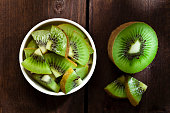 Healthy eating concept: Top view of a round white  bowl filled with kiwi slices shot on rustic wood table. Some kiwi slices are out of the bowl directly on the table. DSRL studio photo taken with Cano