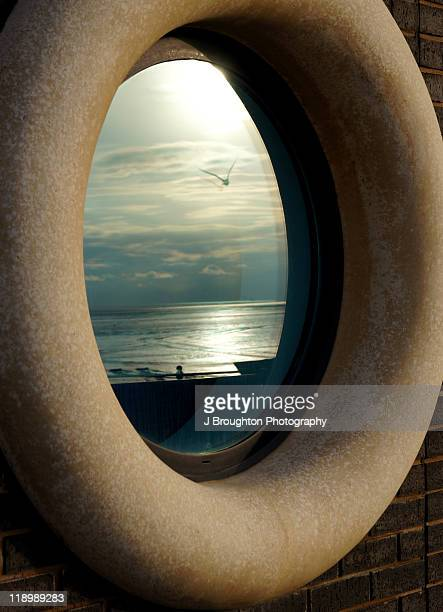 Round window with coastal landscape