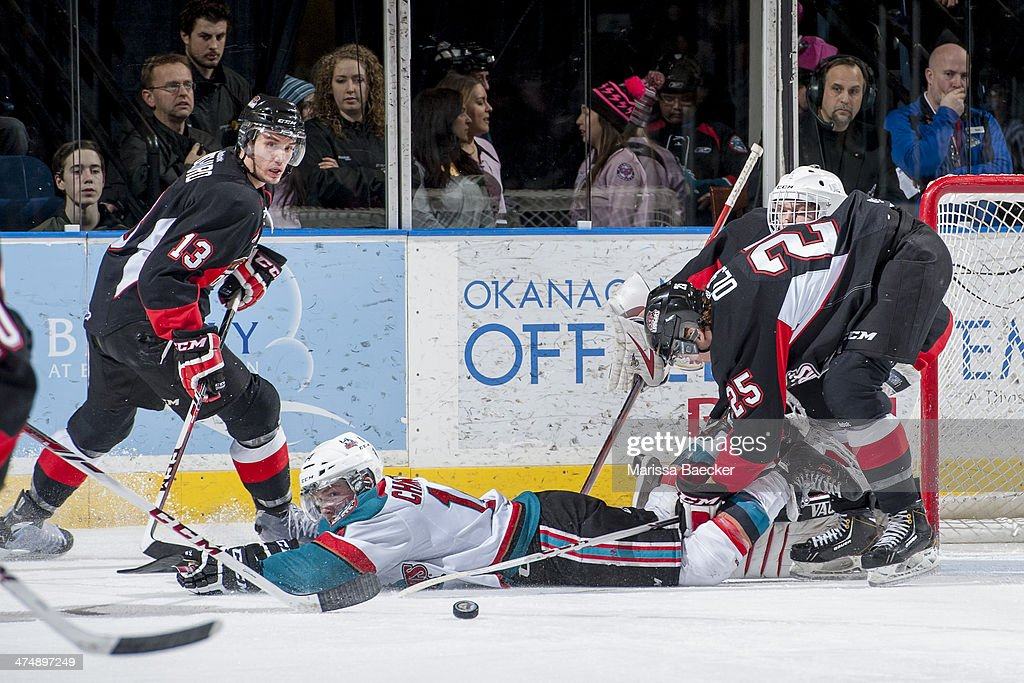 Rourke Chartier #14 of the Kelowna Rockets is checked to the ice by Tate Olson #25 of the Prince George Cougars on February 25, 2014 at Prospera Place in Kelowna, British Columbia, Canada.