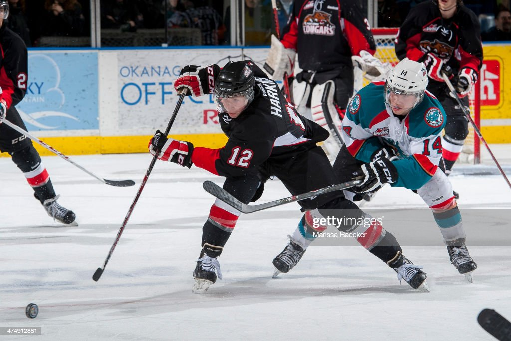 Rourke Chartier #14 of the Kelowna Rockets stick checks Jansen Harkins #12 of the Prince George Cougars during the third period on February 25, 2014 at Prospera Place in Kelowna, British Columbia, Canada.
