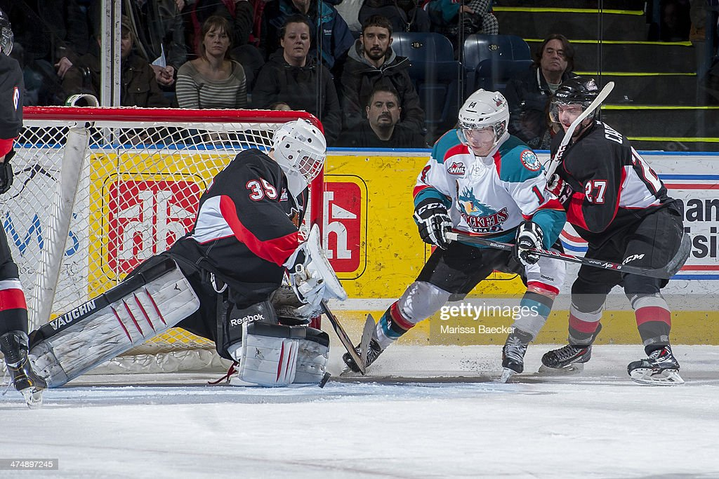 Rourke Chartier #14 of the Kelowna Rockets tries to score a goal on the net of Ty Edmonds #35 as Joseph Carvalho of the Prince George Cougars checks him from behind during first period on February 25, 2014 at Prospera Place in Kelowna, British Columbia, Canada.