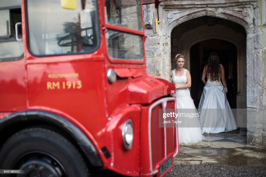 A Routemaster bus is parked outside as debutante Lauren Evans, 27, from Haslemere, looks out of the entrance to Boughton Monchelsea Place ahead of the Queen Charlotte's Ball on September 9, 2017 in Maidstone, England. In 1780 the first debutante's Ball was held by King George III to celebrate the birthday of his wife Queen Charlotte and raised money for a maternity hospital. Society girls were presented to the monarch and it became an annual event and important as a marriage market for the upper echelons of society. The London Season runs for six months of the year including sporting events, cocktail parties, dances and concerts and the Ball is the pinnacle of this season. After the present Queen terminated the practice of introducing debutantes at royal garden parties in 1957, Lady Howard de Walden followed by then editor of Tatler, Peter Townend, continued the tradition and on his death Peter nominated former debutantes Jennie Hallam-Peel and Patricia Woodall to take over running of The London Season. It is now focussed on raising money for children in need worldwide and the Queen Charlotte's Ball has been held in Shanghai and Dubai as well as various grand venues in London. This year the debutantes' gowns have been supplied by Berketex Brides and the cake, to which the debutantes curtsey, is made by Pretty Gorgeous Cakes.
