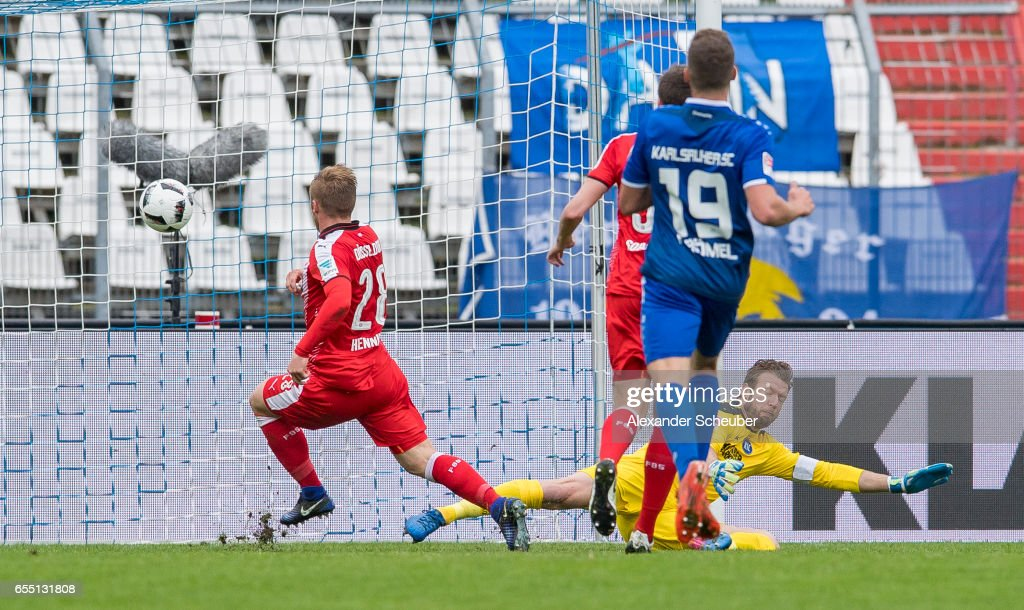 Rouwen Hennings of Fortuna Duesseldorf scores the first goal for his team against Dirk Orlishausen of Karlsruhe during the Second Bundesliga match between Karlsruher SC and Fortuna Duesseldorf at Wildparkstadion on March 19, 2017 in Karlsruhe, Germany.
