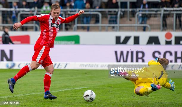 Rouwen Hennings of Fortuna Duesseldorf scores the third goal for his team against Dirk Orlishausen of Karlsruhe during the Second Bundesliga match...