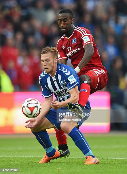Rouwen Hennings of Karlsruher SC holds off Johan Djourou of Hamburger SV during the Bundesliga playoff second leg match between Karlsruher SC and...