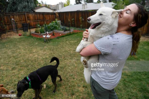 Rover Sitter Hailey Colebank lifts and cuddles with Zola a dog she sits for while her dog Summit left plays with another dog she sits for Lucy far...