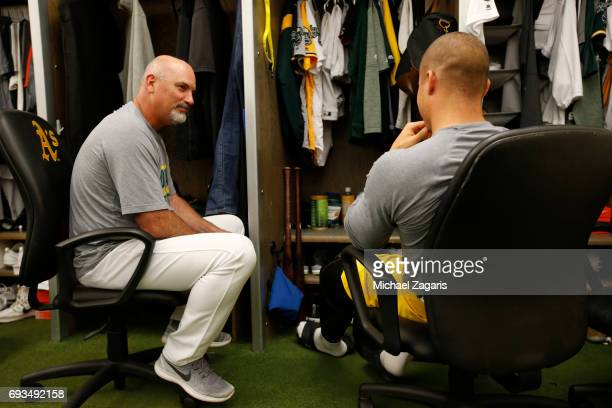 Roving instructor Steve Scarsone of the Oakland Athletics talks with Jake Smolinski in the clubhouse prior to the game against the Miami Marlins at...