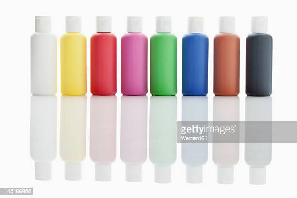 Row of acrylic color bottles on white background