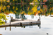 Empty Adirondack Chairs on a Jetty on a Lake in Autumn. Great Reflection of Autumnal Trees in the Calm Waters. Lake Placid, NY.