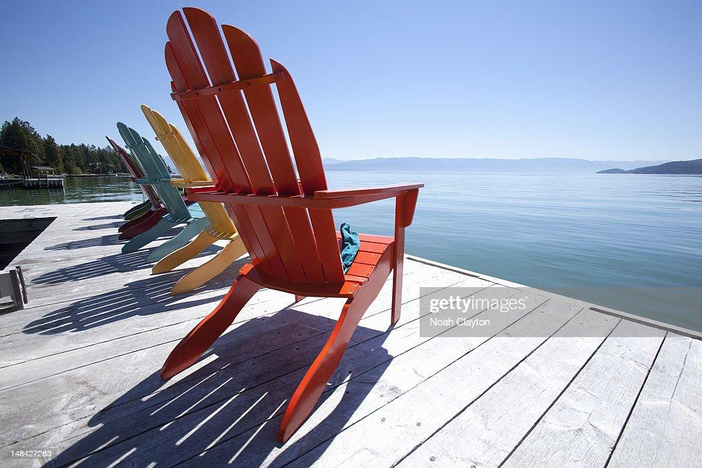 Row of adirondak chairs on dock by scenic lake