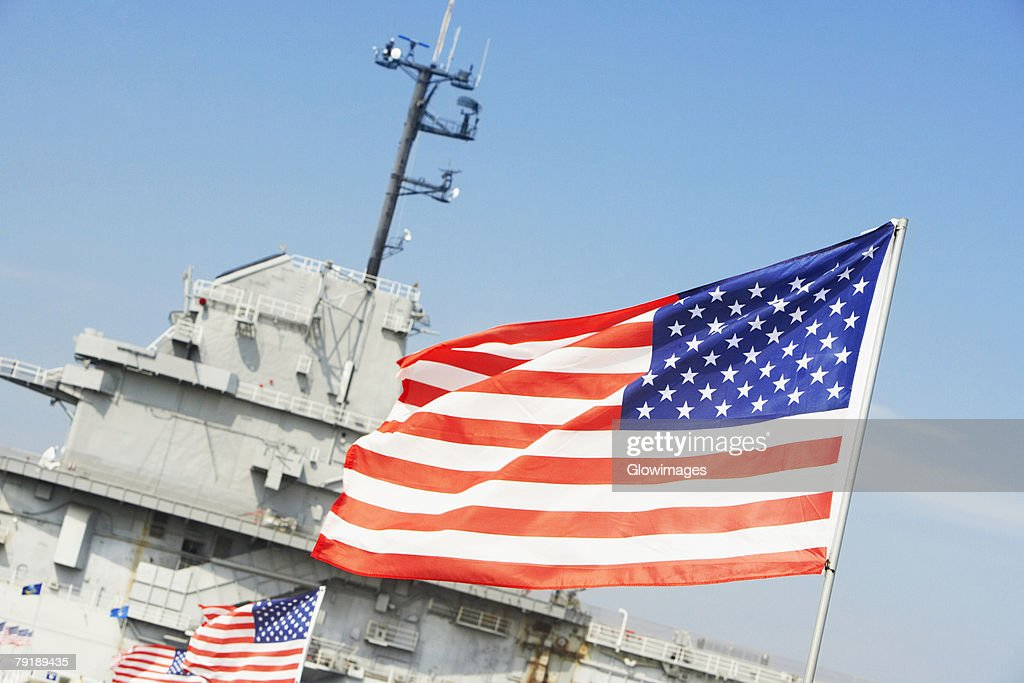Row of American flags fluttering in front of a military ship, Patriot's Point, Charleston Harbor, Charleston, South Carolina, USA : Foto de stock