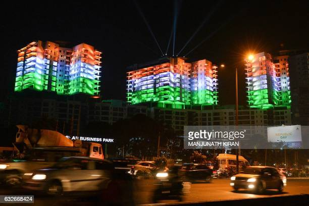 A row of apartment buildings is illuminated with the colours of the Indian national flag on the eve of Republic Day celebrations in Bangalore on...